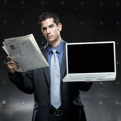 businessman holding a newspaper and a laptop