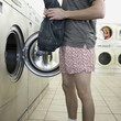 man taking off clothes at a laundromat