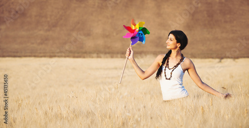 Young beautiful woman in a wheat field with windmill.