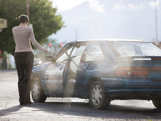 woman standing by her car after an accident