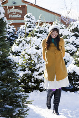 woman standing in the snow in a grove of fir trees