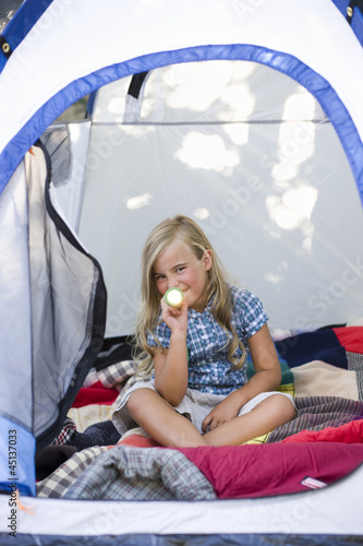 girl sitting in a tent with a flashlight