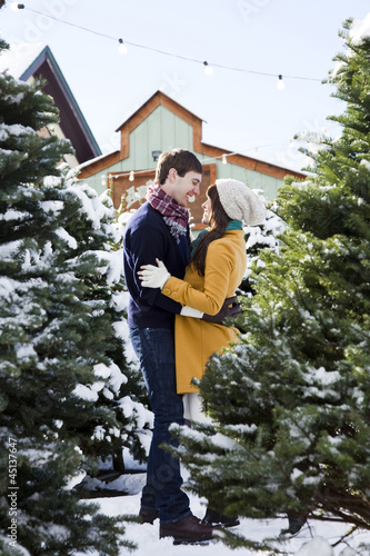 young couple getting a christmas tree in the snow