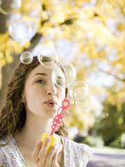 Young woman blowing soap bubbles in Autumn forest