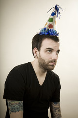 man wearing a party hat looking very depressed