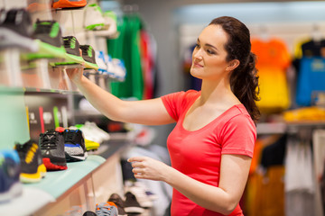 young female sportswear shop assistant working in store