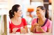 two happy friends having drinks in cafe