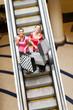 happy shopping women on escalator with shopping bags