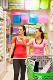 two young women walking in supermarket with trolley