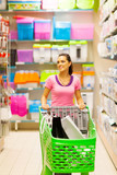young woman walking in supermarket aisle with trolley