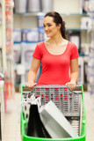 happy young woman pushing a trolley in supermarket
