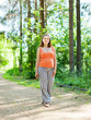 pregnant woman walks on  forest road