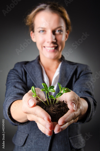 Businesswoman with seedlings and coins