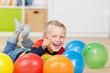 kleiner junge liegt zwischen bunten luftballons