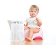 funny baby girl sitting on chamberpot with eyeglasses and newsp