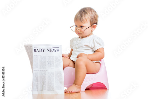 funny baby girl reading newspaper on chamberpot