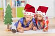 zwei kinder schreiben wunschzettel an das christkind