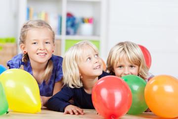 drei mädchen spielen mit bunten luftballons
