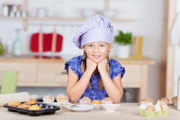 mädchen mit bäckermütze backt muffins