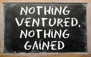 "Proverb ""Nothing ventured, nothing gained"" written on a blackboa"