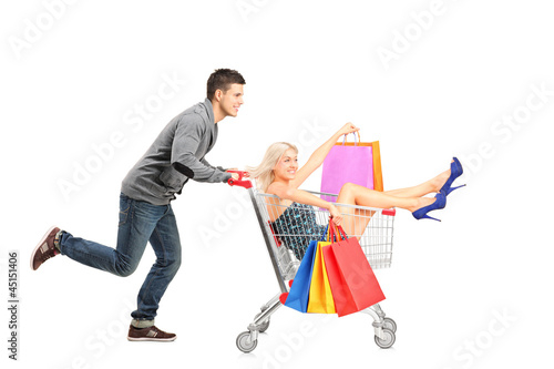 Person pushing a shopping cart, happy woman with bags in it