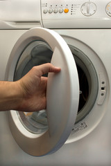man's hand opening  washing machine door