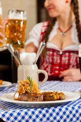 Leute in Tracht essen in bayerischem Restaurant