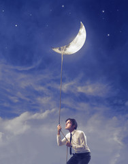 Businessman Holding the Moon