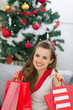 Happy young woman near Christmas tree with shopping bags