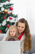 Mother and baby near Christmas tree using laptop