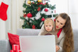 Surprised mother and baby near Christmas tree looking in laptop