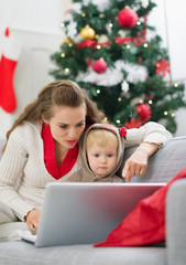 Mother showing baby something in laptop near Christmas tree
