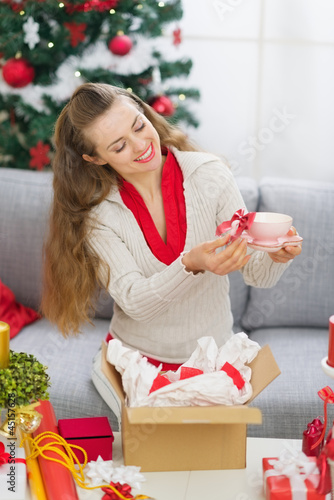 Happy young woman laying on couch near Christmas tree