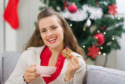 Happy young woman near Christmas tree with cup and cookie