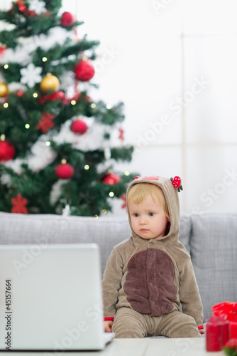 Baby in Christmas deer costume near Christmas tree looking in la