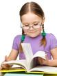 Cute little girl reading book wearing glasses