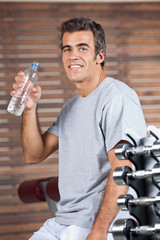 Happy Man Drinking Water From Bottle At Health Club