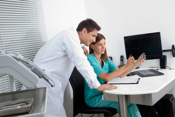 Dentist With Assistant Analyzing Report