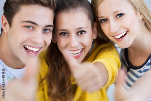 Three young friends with thumbs up