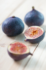 Vertical shot of whole and halved figs on wooden boards