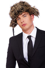 A man wearing a black suit and a fur hat