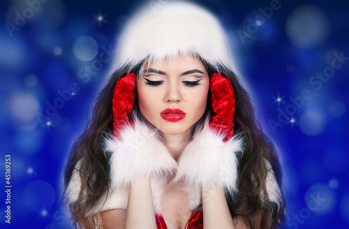 Santa girl listening to the music on blue background