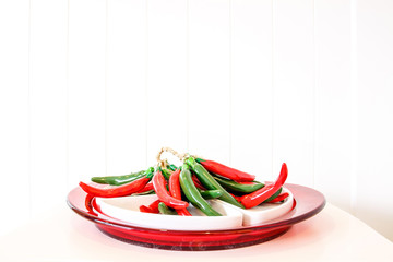 Green and red chili ceramic and glass bowl on white background