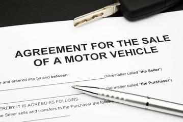 sale of a motor vehicle with car key and pen