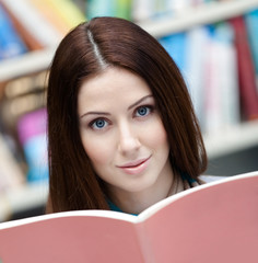 Female student reads the book at the library. Learning