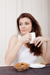 beautiful woman enjoying tea and cookies