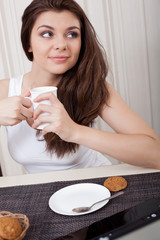 Happy woman enjoying tea and cookies