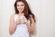 woman near wall holding mug