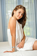 teen girl at home in white dress and relaxing on bed
