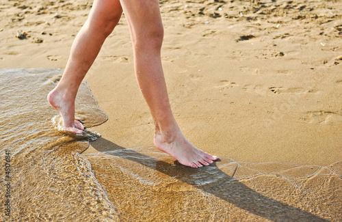 Girl's barefoot legs on the sand beach